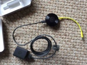 Picture of the Google Chromecast Audio receiver with its audio and power cords connected.