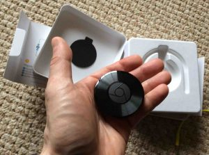 Picture of the Google Chromecast Audio receiver, held in hand.