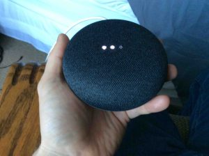 Picture of the Google Mini smart speaker, factory default reset in progress. It showing scanning bright white lights.