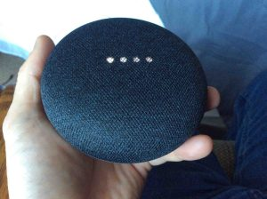 Picture of the Google Home Mini speaker rebooting, showing white scanning lights pattern.
