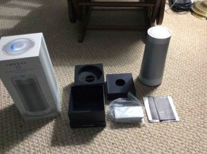 Picture of the Harman Kardon Invoke voice activated speaker, completely unboxed, showing accessories, the speaker itself, and the pamphlets.