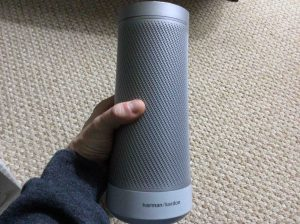 Picture of the Harman Kardon Invoke voice activated speaker, front view, unboxed, held In hand.