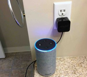 Picture of the Amazon Alexa Echo Gen 2 smart speaker with power adapter, plugged into wall outlet.