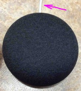 How to turn up volume on Google Home Mini. Picture of the Google Mini speaker, showing top view, with power cord at twelve o'clock.
