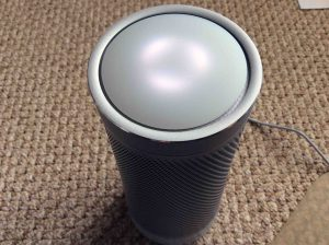 Picture of the Harman Kardon Invoke voice activated speaker, front top view, showing lights displaying Ready for Setup status.