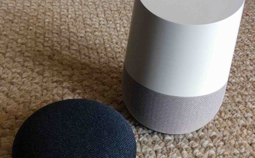 Picture of the Google Home Mini and Original smart speakers together, side by side, front view.
