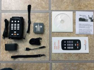 Picture of the HumanWare Victor Reader Trek navigator, showing the contents of the original box, Including the Trek, USB AC power adapter, long and short USB cables, wrist and shoulder straps, earbuds, manual, warranty paper, and DVD disc.