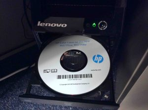 Picture of the HP Color Laserjet Pro MFP M477 driver disc inserted into Lenovo computer.