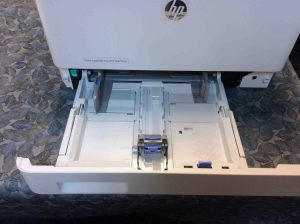 Picture o fthe HP color Laserjet pro MFP M477 series printer, front view, showing lower paper tray open.