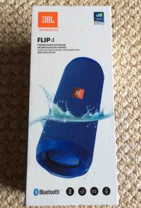 Picture of the JBL Flip 4 waterproof Bluetooth speaker box, front view, showing the speaker dipped in water. JBL Flip 4 portable Bluetooth speaker picture gallery.