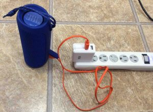 How to Charge JBL Flip 4. Picture of the JBL Flip 4 waterproof speaker, charging from a RavPower USB AC charger.