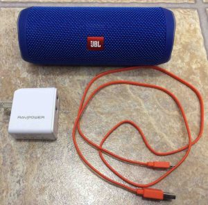Picture of the JBL Flip 4 portable speaker with a RavPower USB charger and micro USB charge cable. JBL Flip 4 portable Bluetooth speaker picture gallery.