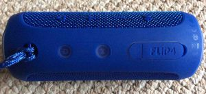 Picture of the JBL Flip 4 wireless speaker, top view, showing speaker controls, horizontal.