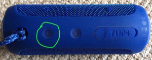 Picture of the JBL Flip 4 speaker turned OFF, with its Power button circled.