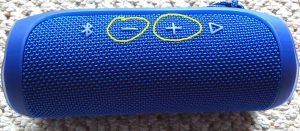 Picture of the JBL Flip 4 Bluetooth speaker. Showing the Volume UP and DOWN buttons circled in yellow.