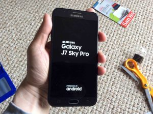 How to reboot Samsung Galaxy J7 Sky Pro TracFone Android phone. Picture of the Samsung J7 TracFone Galaxy Sky Pro Phone, powering up, displaying its introduction screen.
