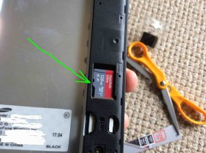 Picture of a new microSD memory card positioned in slot in phone but not yet snapped into place.