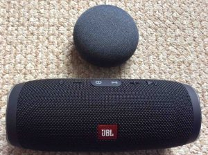 Picture of a Google Home Mini Smart Speaker with a JBL Charge 3 Bluetooth speaker.