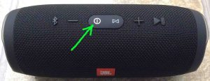 Picture of the JBL Charge 3 Bluetooth speaker, powered On, not paired. Showing the glowing white power button highlighted. JBL Charge 3 power bank Bluetooth speaker review, features, specs.