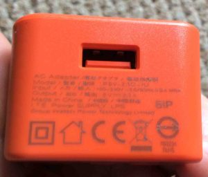 Picture of the JBL Charge 3 rechargeable wireless speaker AC power supply adapter. Showing the USB output port side, with specs printed on that side.