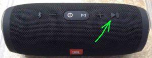 Picture of the JBL Charge 3 waterproof portable speaker. Showing its Play-Pause button highlighted.