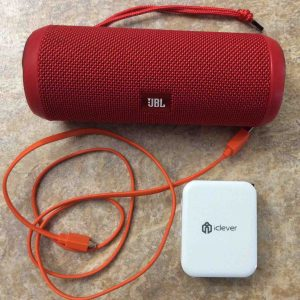 Picture of the JBL Flip 3 battery operated speaker, with its USB charging cable along with an iClever 3 port USB wall charger.