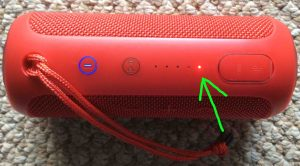 Picture of the JBL Flip 3 Bluetooth speaker, its battery status indicator showing that the internal battery is almost completely dead. The red light, showing that the battery is critically low, is highlighted. How to Charge JBL Flip 3 splashproof Bluetooth speaker.
