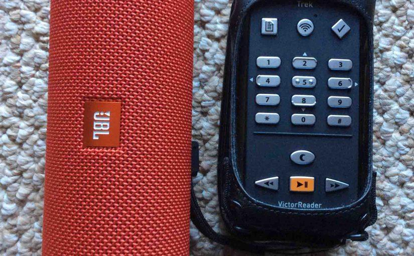 Picture of a JBL Flip 3 Bluetooth speaker alongside a Victor Reader Trek talking GPS audio media player.