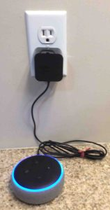 Picture of the 3rd Generation Echo Dot smart speaker powering up, showing its AC adapter plugged into standard wall outlet.