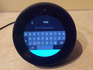 Picture of the speaker, displaying its WiFi Password Entry screen, with blank field, no password entered yet. How to Set Up Alexa Echo Spot.