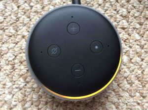 Picture of the Amazon Echo Dot 3rd Generation speaker, shown in Setup mode, light ring orange and spinning.