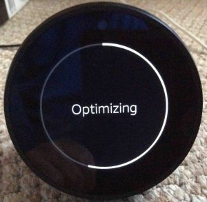 Picture of the Amazon Echo Spot Alexa speaker, in middle of Optimizing operation.