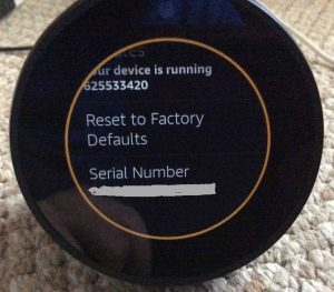 Picture of the Amazon Echo Spot speaker, showing orange light ring as Factory Reset operation starts.
