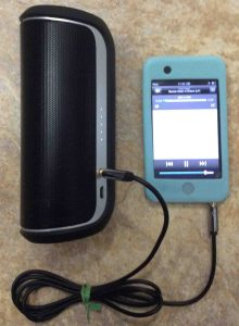 Picture of the JBL Flip 2 Bluetooth speaker, playing from an iPod Touch via its AUX input port.