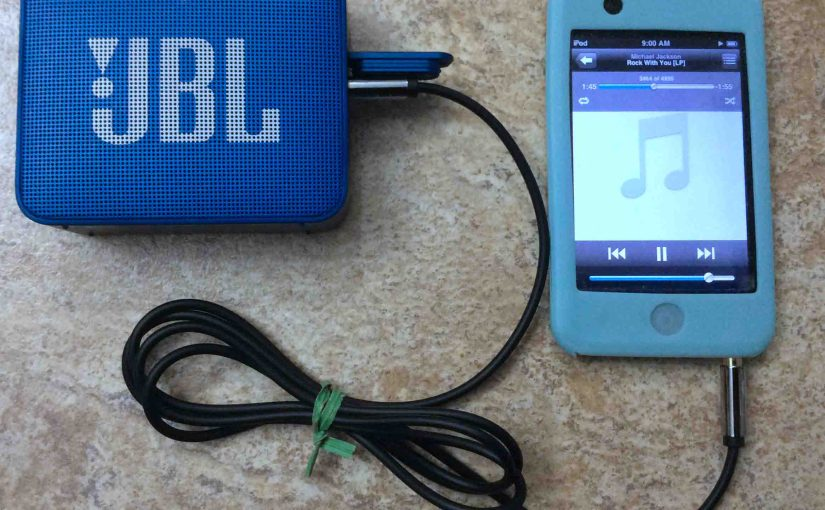 Picture of the JBL Go 2 Bluetooth speaker, connected via its AUX input to an iPod Touch portable media player.