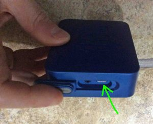 Picture of the JBL Go 2 Bluetooth speaker, right side view, showing its port door held open with finger.