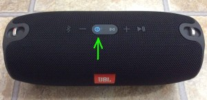 Picture of the JBL Xtreme Bluetooth speaker powered on and in pairing mode, with its blue glowing Power button highlighted.