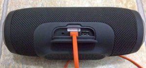 Picture of the Charge 3 JBL power bank speaker, back view, its port door open, with the USB charging cord inserted.