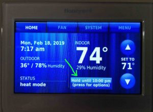 Picture of the thermostat displaying its -Home- screen, with the -Hold- button showing -Temporary Hold- mode highlighted.