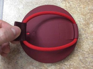 Picture of the UE Roll speaker, back view, showing the built in bungee loosened.