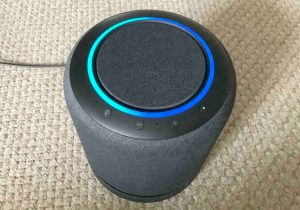 Front top view picture of the Echo Studio Alexa, showing the blue green light ring as the speaker boots.