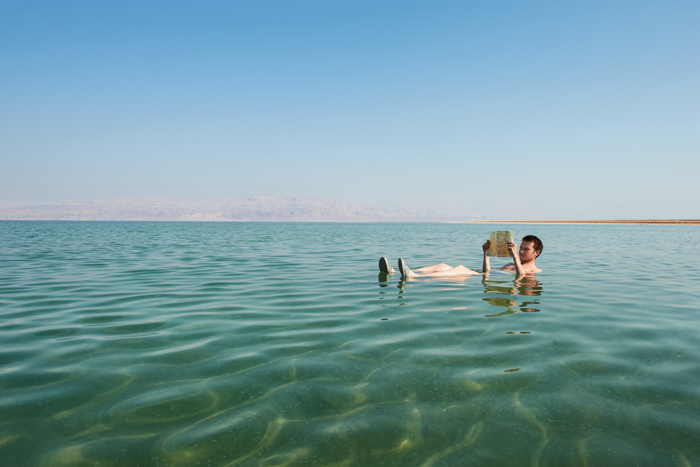 A man floats on the Dead Sea while reading a book