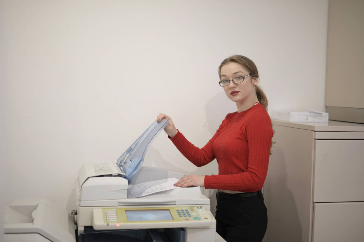 serious female office worker using printer in workplace