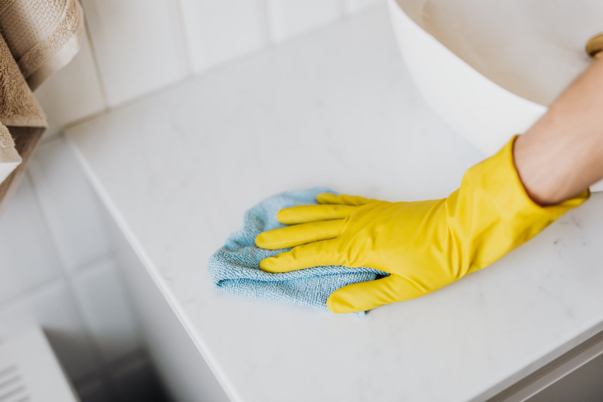crop person cleaning tabletop in bathroom