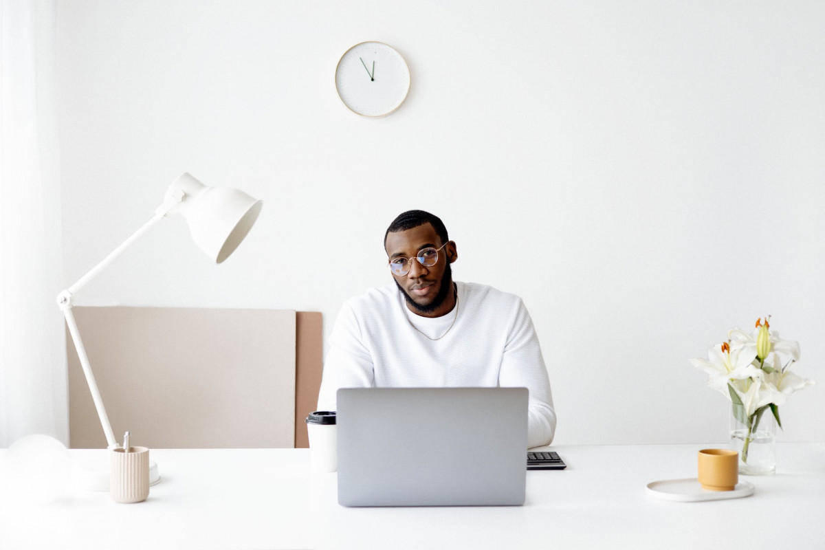 photo of man wearing white sweater in front of laptop