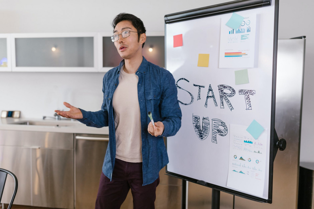 man in blue button up shirt and blue denim jeans standing beside white board
