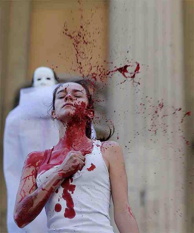 An actress splashes red paint on herself during a protest by Grupo Fazendo Certo (Group Doing Right) and non-governmental organization Rio de Paz (Rio of Peace) in support of victims of violence, in front of the Rio de Janeiro State Assembly. According to Rio de Paz, 35,000 victims of violence have been missing in the Rio de Janeiro state since 2007.