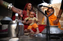 Tulsi Devi (l), wife of farmer Jay Ram, prepares tea at their home.
