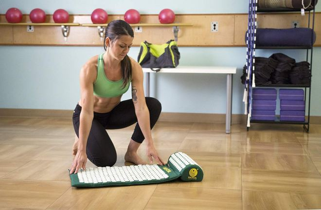 woman with acupressure mat to relieve muscle soreness