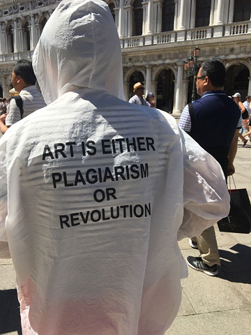 someone seen from behind wearing a white hoodie with the text ART IS EITHER PLAGIARISM OR REVOLUTION